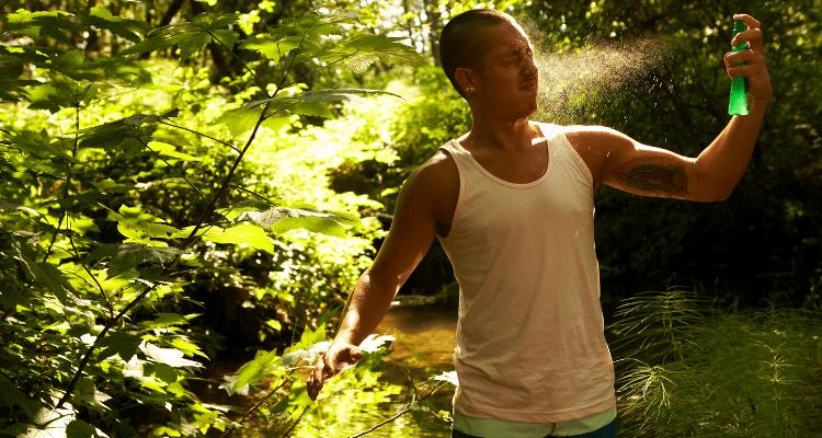 hiker spraying tick repellent on himself